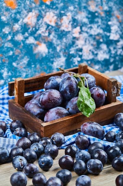 Cestino di legno delle prugne fresche sull'azzurro. Foto Gratuite