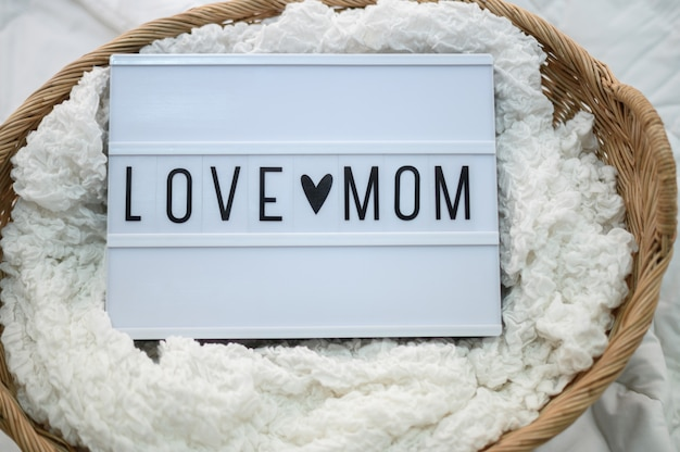 Wooden basket with fabric and mom love sign Free Photo