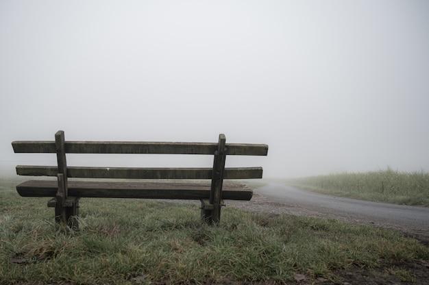 霧-孤独の概念で覆われた道路の近くの木製のベンチ 無料写真