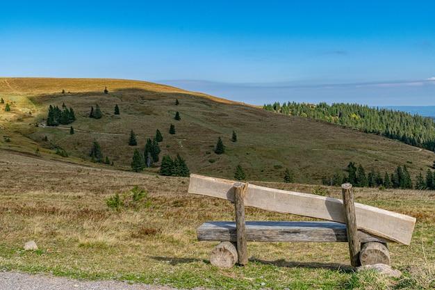 澄んだ青い空の下でのトレッキングやハイキングに最適な丘の上の木製ベンチ 無料写真