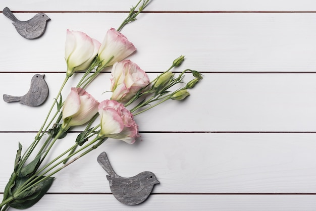 Wooden birds with bunch of eustoma flowers on white textured background Free Photo