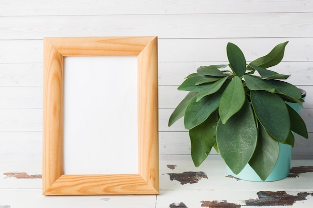 Wooden blank picture frame and green flowers on white background. Premium Photo