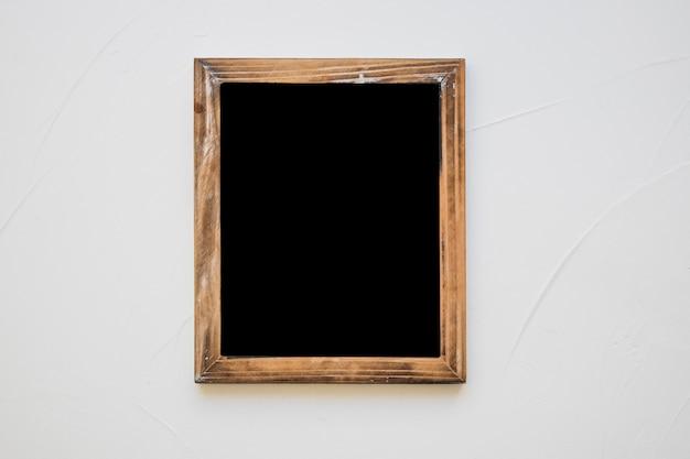 Wooden blank slate on white wall
