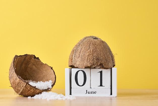 木製ブロックカレンダーと黄色に分離されたココナッツ Premium写真
