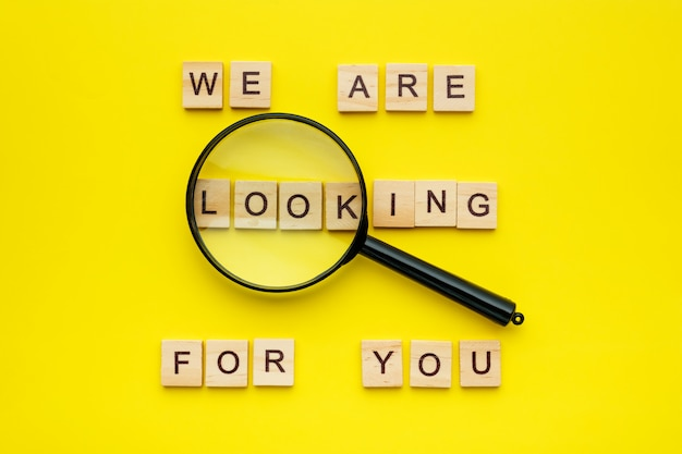 Wooden block lettering we are looking for you and magnifying glass on yellow background. Premium Photo
