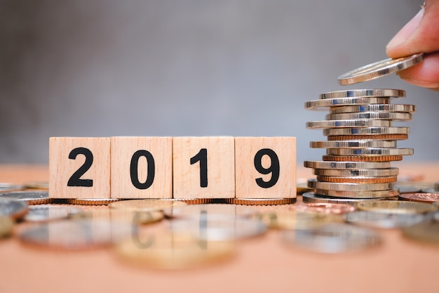 Wooden block year 2019 with hand holding stack coins Premium Photo