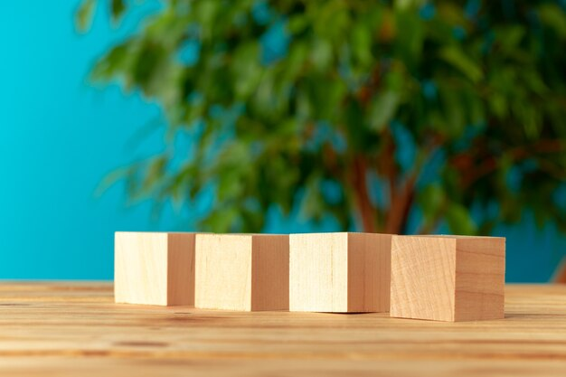 ぼやけた植物の背景、正面図に対して机の上の木製ブロック Premium写真