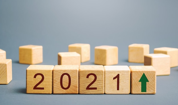 Wooden blocks with the inscription 2021 and an up arrow Premium Photo