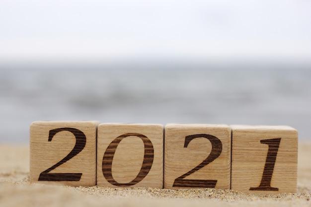 Деревянные блоки с номерами 2021 расположены на песке на пляже. Premium Фотографии