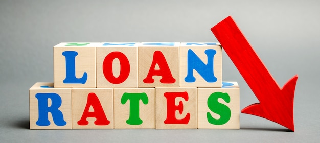 Wooden blocks with the word loan rates and arrow down. the  of low mortgage rates. Premium Photo
