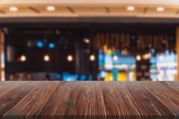 Wooden board over blurred inside of restaurant background Premium Photo