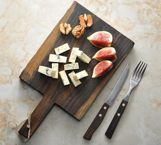 On a wooden board, cheese with blue mold dorblu, a few figs and walnuts. Premium Photo