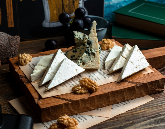 Wooden board of different cheeses and walnuts Free Photo