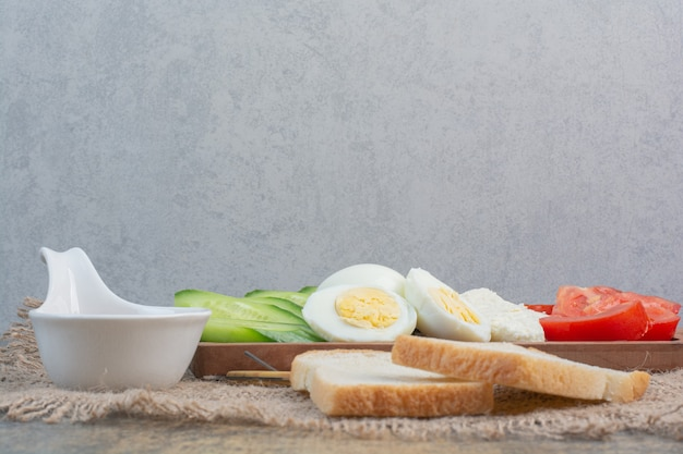 Wooden board of eggs, cheese and vegetables with bread. Free Photo