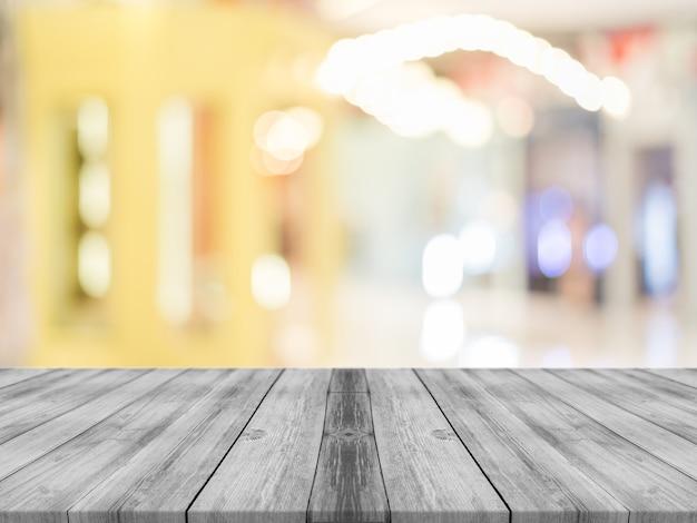 木の板の空のテーブルは、コーヒーショップのバックグラウンドでぼかし。 Premium写真