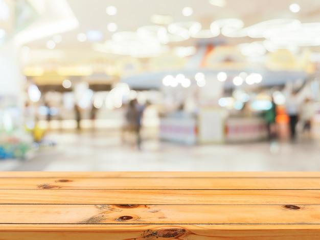 木の板の空のテーブルは、デパートの背景にぼかし。 Premium写真