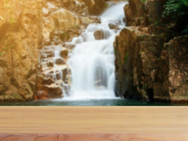 木の板の空のテーブルは、森のバックグラウンドで滝をぼかし。 Premium写真