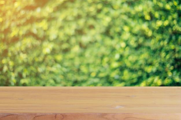 木の板の前に空のテーブルが森の背景で木をぼかし。 Premium写真