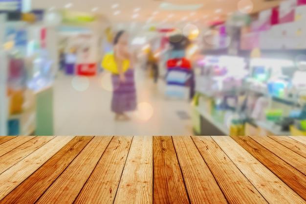 배경 흐리게 앞 나무 보드 빈 테이블. 슈퍼마켓에서 흐림 효과가있는 전망 가벼운 나무-디스플레이에 사용하거나 제품을 몽타주 할 수 있습니다. 제품 표시를 위해 조롱하십시오. 프리미엄 사진