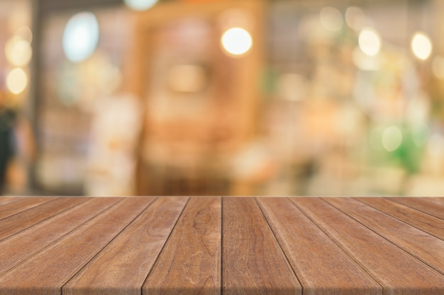 ぼやけているコーヒーショップの背景の前に木の板の空のテーブル。 Premium写真