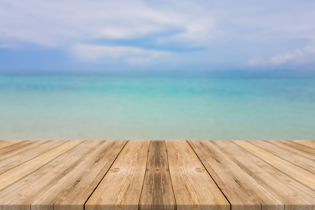 Wooden board empty table top blur sea sky background Perspective