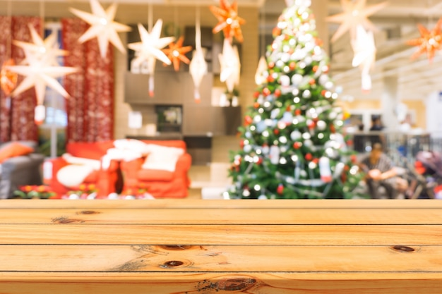 Wooden board empty table top on of blurred background. Perspective brown wood table over blur christmas tree and fireplace background, can be used mock up for montage products display or design layout Free Photo