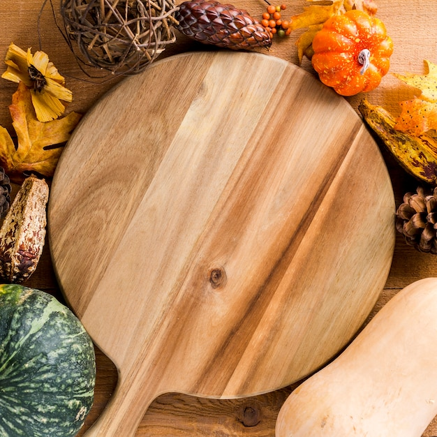 Wooden board framed by autumn harvest Free Photo