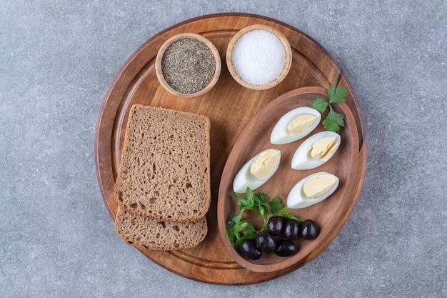Una tavola di legno con uova sode e fetta di pane. foto di alta qualità Foto Gratuite