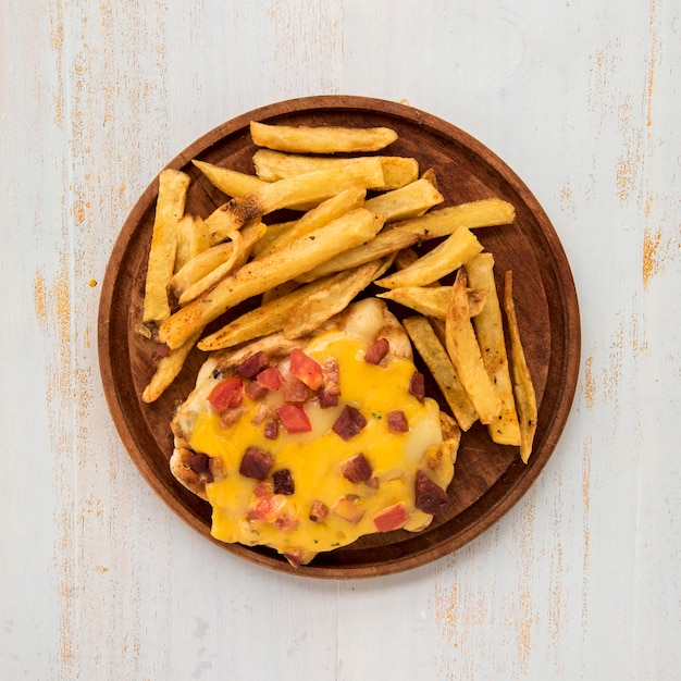 Wooden board with french fries and omelette on painted desk Free Photo