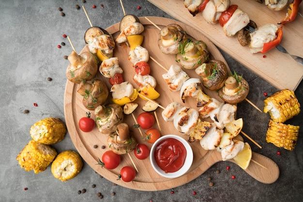 Tavola di legno con pollo alla griglia e spiedini di verdure sul tavolo Foto Gratuite