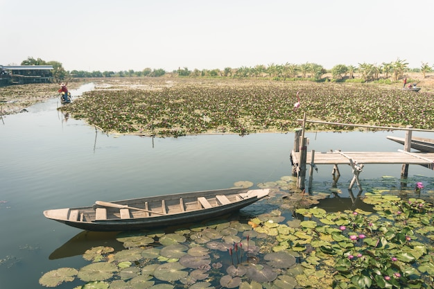 A wooden boat in the beautiful morning lotus field on the lake in a province near bangkok, thailand. Premium Photo