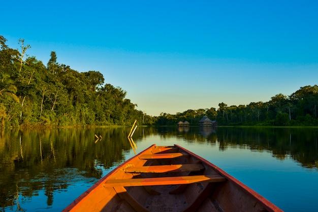 Деревянная лодка посреди озера с голубой водой, вода спокойная и отражает небо и горы. Premium Фотографии