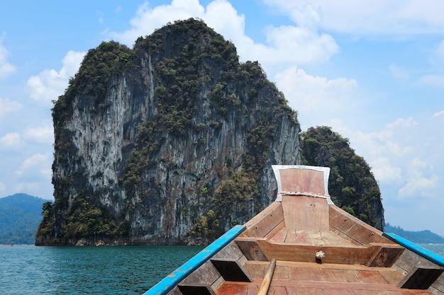 青い曇り空の下で奇岩に囲まれた海に木製のボート 無料写真