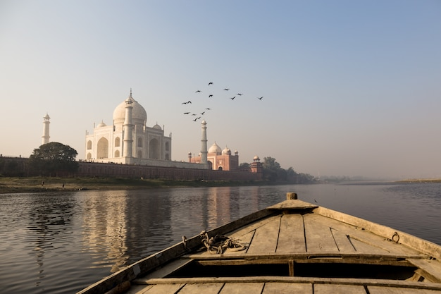 Wooden boat on the yamuna river with taj mahal and bird fly over. Premium Photo