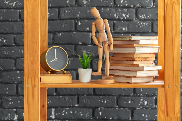 Wooden bookshelf with books and stuff against black brick wall Premium Photo