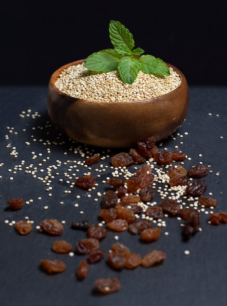 Wooden bowl filled with quinoa on black Premium Photo