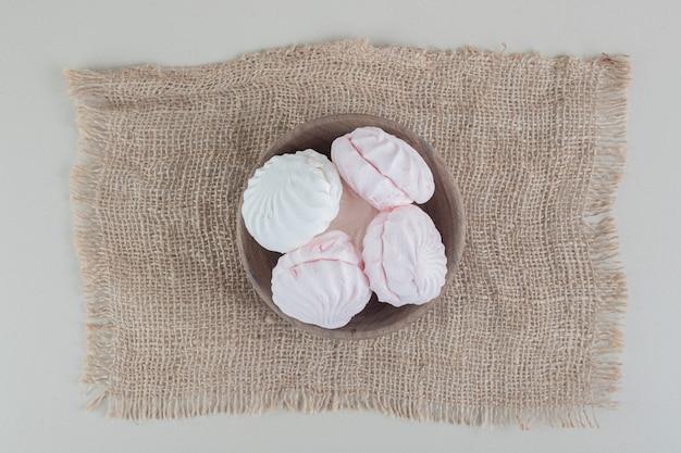Una ciotola di legno piena di zefiri bianchi e rosa. Foto Gratuite