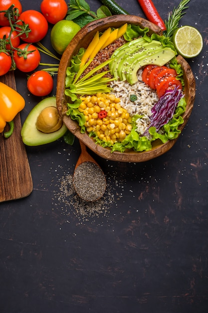 Wooden bowl with chickpea, avocado, wild rice, quinoa, bell pepper, tomatoes, greens, cabbage, lettuce on dark stone table and wooden spoon with chia seeds. top view with copyspace. Premium Photo