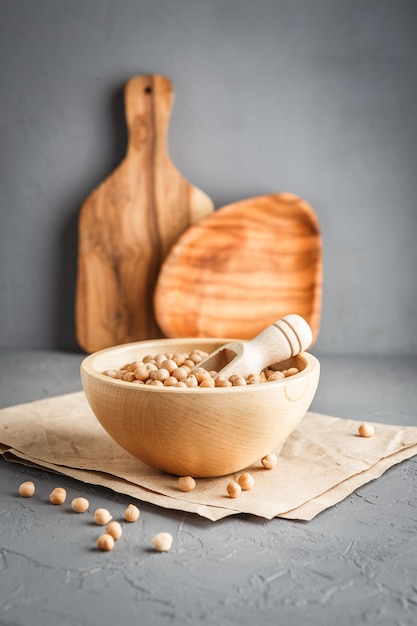灰色のコンクリートの背景に乾燥生有機ひよこ豆と木製のボウル Premium写真