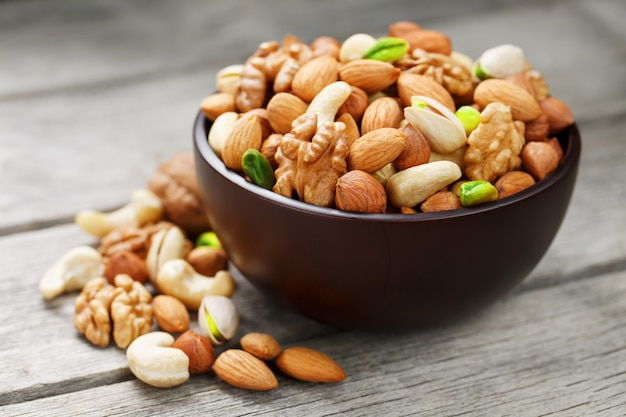 Wooden bowl with mixed nuts on a wooden gray surface Premium Photo