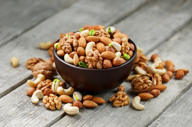 Wooden bowl with mixed nuts on a wooden gray . walnut, pistachios, almonds, hazelnuts and cashews, walnut. Premium Photo
