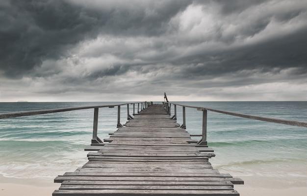 木製の橋と暗い雨の曇り低照明の海。 Premium写真