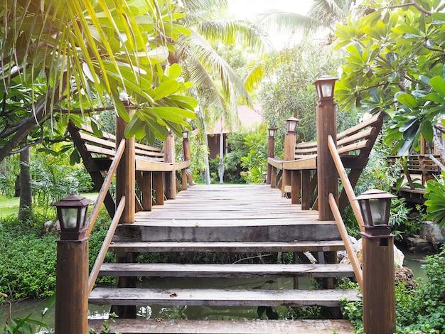 Wooden bridge crossing small canal at green garden decoration. Premium Photo