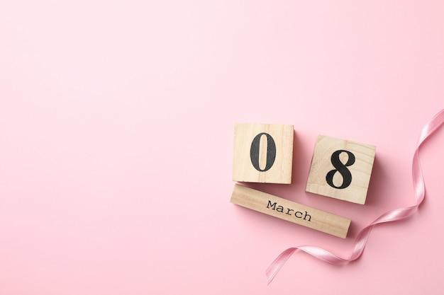 木製のカレンダーとピンクの背景、テキスト用のスペースにリボン Premium写真