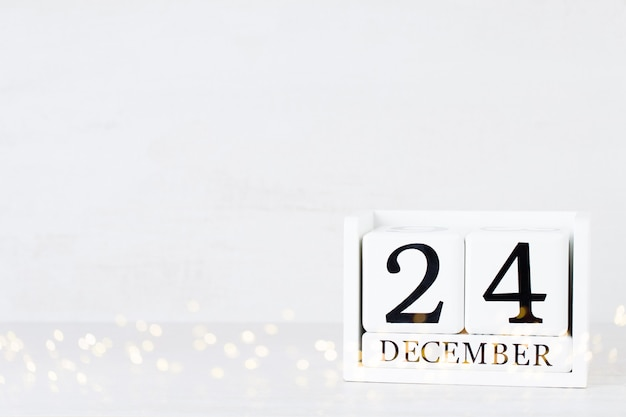 木製カレンダー12月24日のクリスマスの日。クリスマスの装飾が施されたグレー。 Premium写真