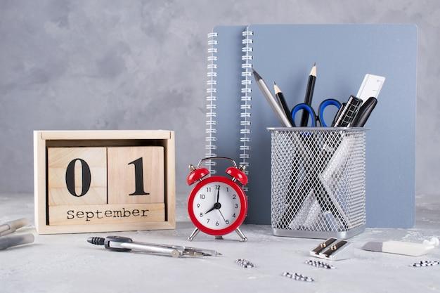 Деревянный календарь, группа школьных принадлежностей, красный будильник на сером столе Premium Фотографии