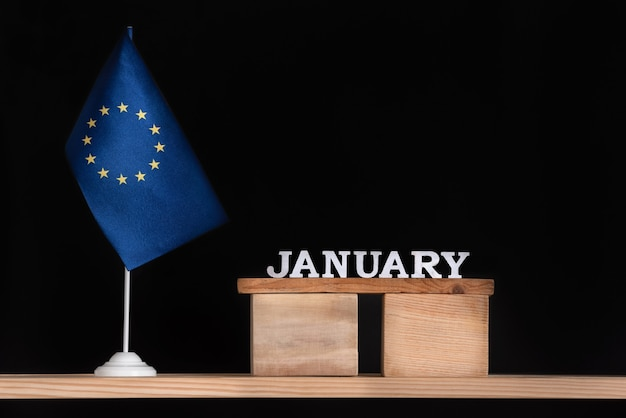 Wooden calendar of january with flag eu on black space. holidays of european union in january. Premium Photo