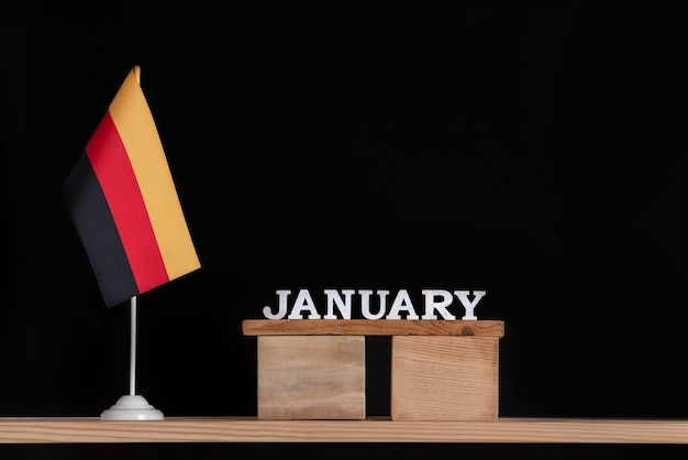 Wooden calendar of january with german flag on black space. holidays of german in january. Premium Photo