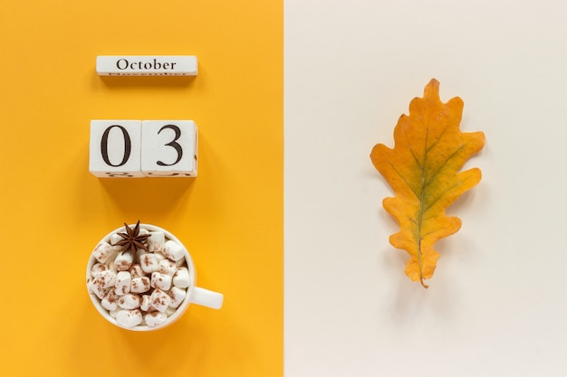 Wooden calendar october 3, cup of cocoa with marshmallows and yellow autumn leaves Premium Photo