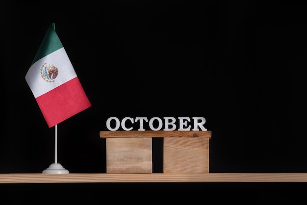 Wooden calendar of october with mexico flag on black background. holidays of mexico in october. Premium Photo